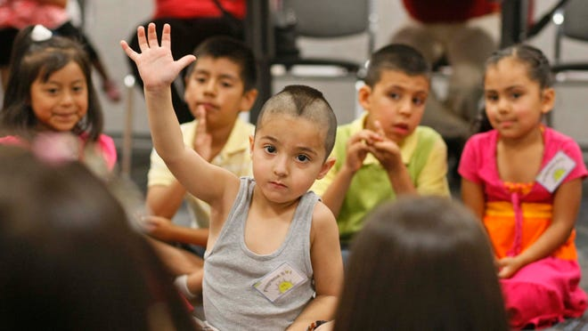 Angel Gonzalez, 4, raises his hand to answer a question before taking a tour of the Salem Public Library on Thursday, July 5, 2012. The tour, put on the the Salem-Keizer Coalition for Equality, is part of a pilot project to increase literacy rates. Students take field trips during the summer that emphasize reading and learning.