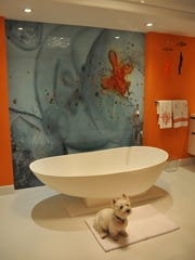 Lily, a white westie, poses in front of the decorative art panels in the master bathroom.