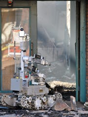 A robot from the explosives disposal unit at the Monterey County Sheriff's Office begins to enter the burned-out shell of the Dick Bruhn building, destroyed in a suspicious fire on Saturday.