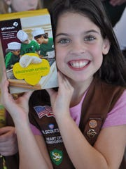 Katrina Richardson of Brownie Troop 80067 holds a box of Savannah Smiles Girl Scout cookies at an event at Jennings Chevrolet Buick GMC on Saturday, Feb. 27.