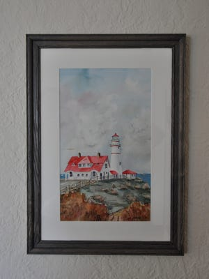 A finished frame houses a watercolor painting.