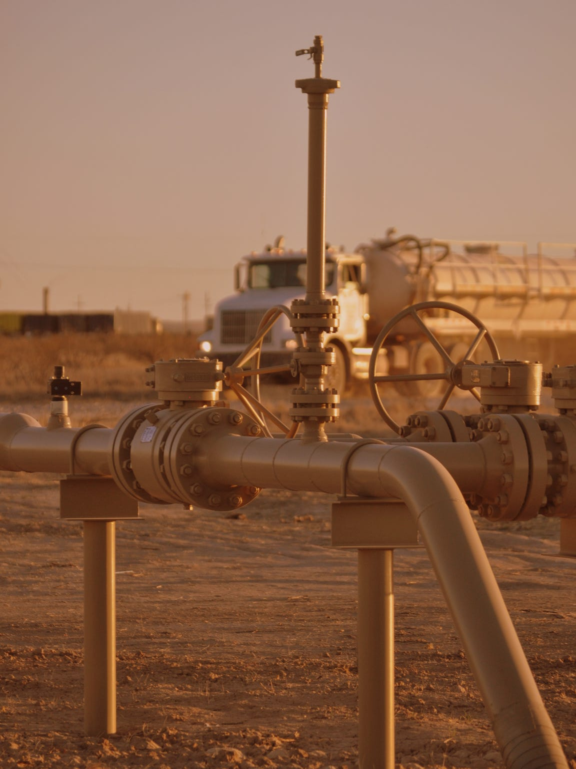 Pressure pipelines rise above the ground near an extraction
