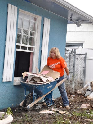 Debra Shock, of Mississippi, hauls pieces of drywall to a debris pile outside a Bonita Springs home as part of hurricane recovery efforts by Samaritan's Purse.
