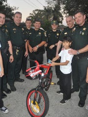 Lee County deputies distributed awards to young essay winners on Dec. 21 in Bonita Springs. Deputies give Juan Fernandez, 10, a new bicycle. Juan is a fifth grader at Bonita Elementary School who won an essay contest.