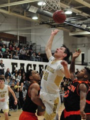 Abilene High's Nic Marczynski goes up for a layup over a pair of Haltom City Haltom defenders during the Eagles' 62-59 win Friday, Jan. 13, 2018, at Eagle Gym.