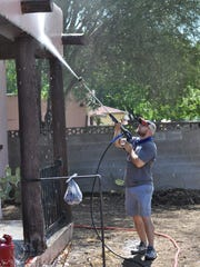 James Felts with Christ the King Cathedral in Texas sprays the front of the house Monday, June 4, 2018, in the 1000 block of Albert. The church is participating in Mission Carlsbad this year.