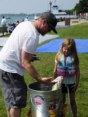 Ryan and Delaney Jones, 6, bring in a large sheepshead to be weighed  during the kids fishing contest Saturday, June 30, 2018, at the Algonac Pickerel Tournament.