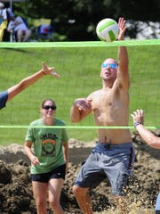A player blocks a shot during a mud volleyball tournament