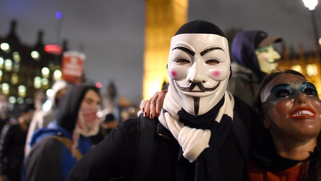 Masked protesters pose in front of the Houses of Parliament during the Million Mask March in Trafalgar Square on Nov. 5, 2015 in London. The anti-establishment protest is organized annually by the hacktivist  group Anonymous.