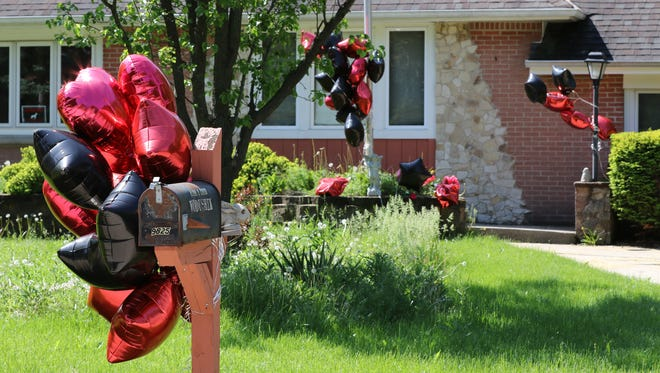 Red and black Mylar balloons attached to a mailbox, trees and light at 9825 Ruby Avenue, the site of a fatal shooting of a 24-year-old man on May 29.