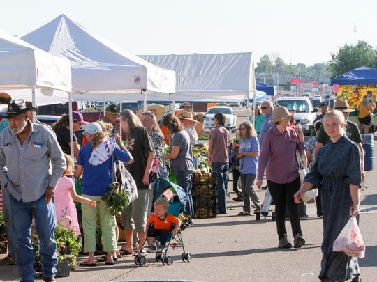Community members shop Saturday at the Farmington Growers Market outside the Farmington Museum at Gateway Park.