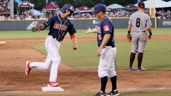 Arizona's Ryan Aguilar, left rounds third base and is congratulated by Arizona head coach Jay Johnson, right after hitting a home run in the eighth inning of their NCAA super regional baseball championship tournament game against Mississippi State in Starkville, Miss., Saturday, June 11, 2016. Arizona won 6-5 in 11 innings.
