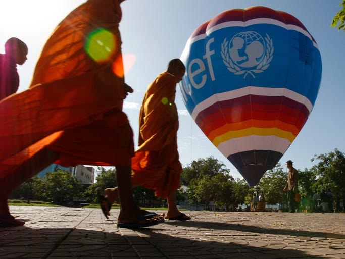 """Buddhist monks walk near a hot air balloon in the preparation of the launch of the """"Flying High for Kids World Balloon Project"""" with UNICEF in Phnom Penh, Cambodia, Tuesday, July 1, 2014. The overland hot air balloon on Tuesday journeyed in Cambodia to increase awareness of children?s right to education and to raise funds for UNICEF's work. (AP Photo/Heng Sinith)"""