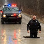 This Michigan pothole is so big, a police officer fits inside