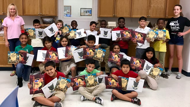 Second-grade children enjoy their book selections thanks to K is for Kids.
