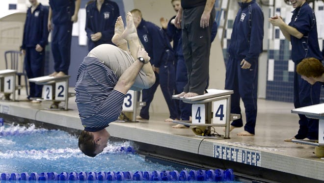 Pittsford coach Rick Schmitt dives into the pool after his swimmers won the sectional title at the NYSPHSAA Section V Class A Swimming & Diving Championships held at the Webster Aquatic Center on Thursday, February 12, 2015.