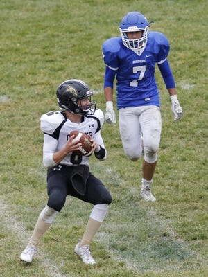 Corning quarterback Owen Gudenrath prepares to pass while hounded by Peter Whitson of Horseheads i nthe third quarter of Saturday's Section 4 game at Horseheads.