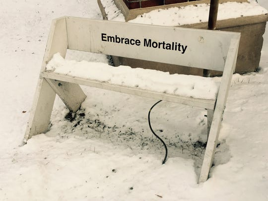 A white bench in the 3100 block features a mysterious inspirational message.
