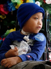 Ricky Solis, 6, looks out the window as his mother