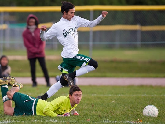 Winooski's Lek Nath Luitel (top) dribbles past Peoples goalie Joe Buonnano during the Division III semifinals on Tuesday afternoon in Winooski.