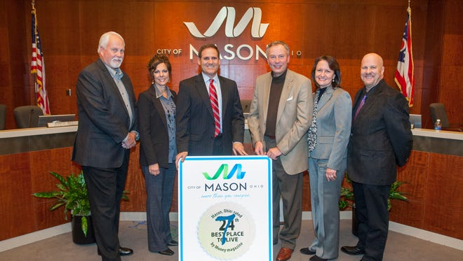 The city of Mason gifted outgoing councilman Tom Grossmann with a large sign proclaiming Mason as Money Magazine's 7th Best Place to Live. Grossmann, third from left, is surrounded by Mason council members, from left: Don Prince, Char Pelfrey, Mayor David Nichols, Barbara Berry-Spaeth and Rich Cox.