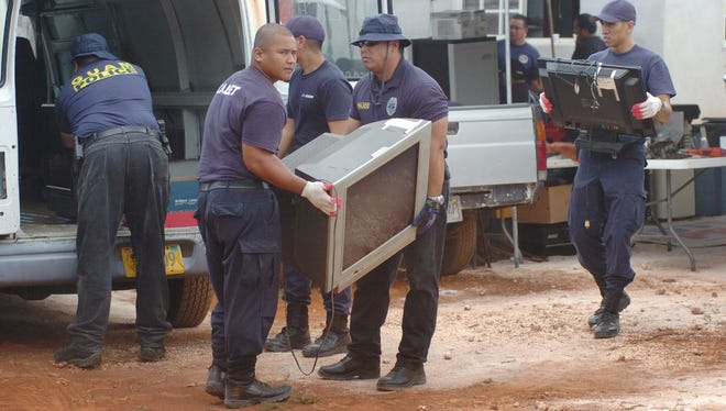 In this April 20, 2017 file photo, Guam Police officers and cadets prepare allegedly stolen items for transport from an Astumbo, Dededo, residence which was raided a day prior. The raid resulted in drug charges against Lourdes and Raymond Duenas. Lourdes Duenas' sentence was commuted by President Barack Obama on Jan. 19, 2017, mainland time.