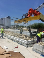 Workers at an industrial site in Titusville construct an artificial reef that will be used to make up for natural offshore rock reefs that will be partially buried in future beach renourishment of Satellite Beach and Indian Harbour Beach.