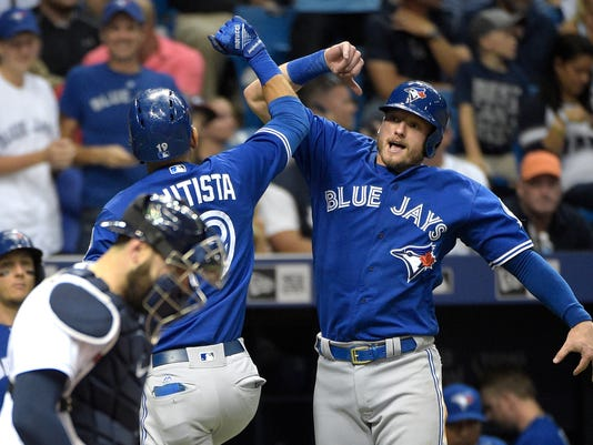 Toronto Blue Jays' Jose Bautista (19) is congratulated by Josh Donaldson, right, after Donaldson scored off Bautista's two-run home run, as Tampa Bay Rays catcher Curt Casali stands at home plate, during the third inning of a baseball game in St. Petersburg, Fla., Saturday, April 30, 2016. (AP Photo/Phelan M. Ebenhack)