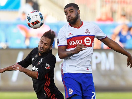 Toronto FC's Jordan Hamilton, right, and D.C. United's Marcelo Sarvas vie for the ball during the first half of an MLS soccer match in Toronto on Saturday, July 23, 2016. (Frank Gunn/The Canadian Press via AP)