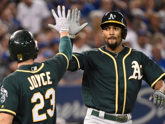 Oakland Athletics Marcus Semien, right, celebrates his two-run home run with Matt Joyce during the fifth inning agianst the Toronto Blue Jays in a baseball game Wednesday, July 26, 2017, in Toronto. (Nathan Denette/The Canadian Press via AP)