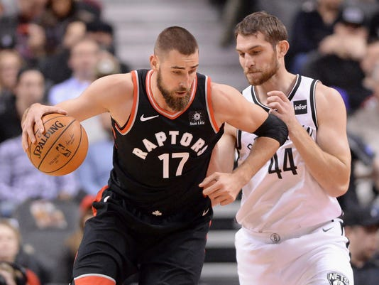 Toronto Raptors center Jonas Valanciunas (17) dribbles the ball under pressure from Brooklyn Nets center Tyler Zeller (44) during the first half of an NBA basketball game, Friday, Dec. 15, 2017 in Toronto. (Frank Gunn/The Canadian Press via AP)
