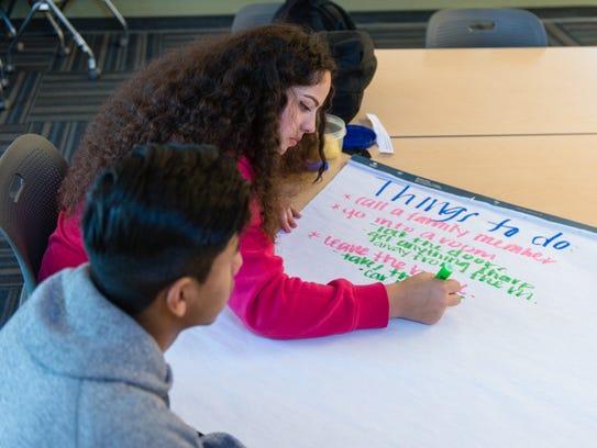 Elizabeth Ochoa, 17, and Victor Ramirez, 17, work on