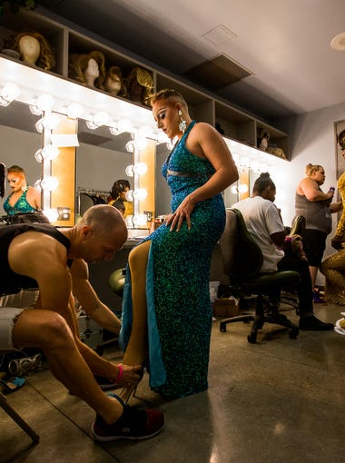 """Gavin Sisson (left) helps his husband Payda Parc, both of Phoenix, put on a heel before the evening wear potion of the Miss Gay Arizona 2018 pageant on Sunday, June 17, 2018 at the Tempe Center for the Arts in Tempe, Arizona. """"I love being able to be go out and represent the system and be a role model at the same time,"""" Parc said."""