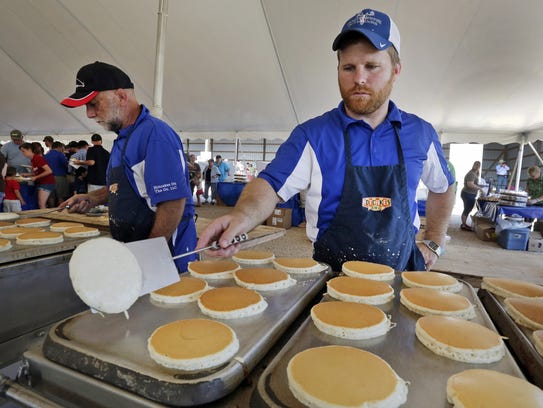 Joe Potter of Hartford, right, flips pan cakes during
