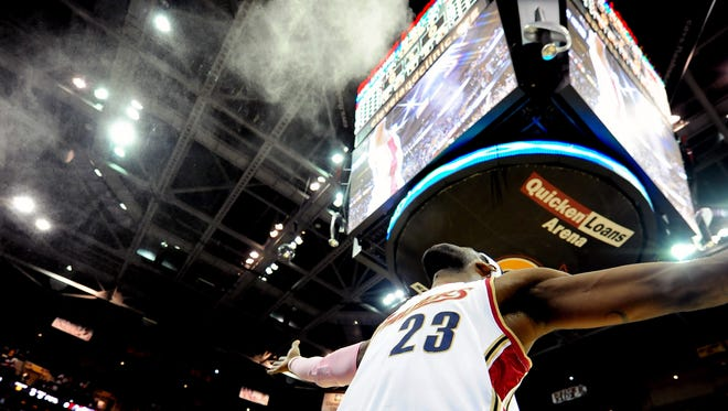 Cleveland Cavaliers forward LeBron James (23) throws chalk into the air prior to the game against the Chicago Bulls at Quicken Loans Arena.