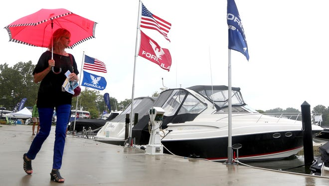 The very small amount of people that were at the boat show many walked around with umbrellas as they looked at the various kinds of boat on display Saturday.