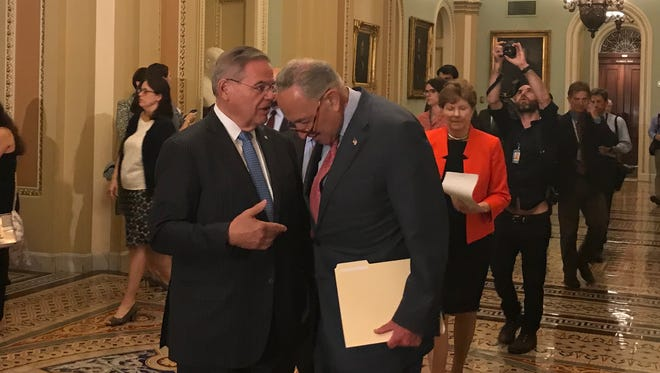 Sen. Bob Menendez, lD-N.J., speaks into the ear of Senate Minority Leader Chuck Schumer, D-N.Y., before they address reporters at a news conference about President Trump's meeting with Russian President Vladimir Putin on July 17, 2018.