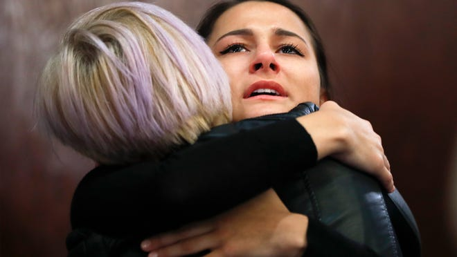 Bailey Kowalski hugs a friend after a news conference in East Lansing in April. The then-22-year-old Michigan State University student was speaking publicly a year after suing the school, alleging that three men's basketball players raped her in 2015 and that she was discouraged by counseling center staff from reporting what happened. (AP Photo/Paul Sancya)