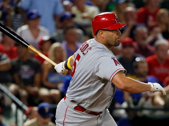 FILE - In this Sept. 1, 2017, file photo, Los Angeles Angels' Albert Pujols follows through on a two-run single that came off a pitch from Texas Rangers starting pitcher Cole Hamels in the fifth inning of a baseball game in Arlington, Texas. Angels' Shohei Ohtani will likely work as part of a six-man starting rotation and then share DH duties with Pujols when not on the mound. (AP Photo/Tony Gutierrez, File)