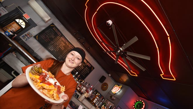 Tiffany Lyons, manager of the Horseshoe Bar & Grill, displays the popular Irish Nachos, which are waffle fries covered in cheese, salsa, tomatoes, and sour cream and come with jalapeno caps.