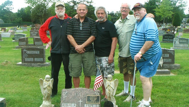 Pictured standing at the grave marker of veteran Peter Hall are, from left: Mike Fane, Jeff Hightower, John Marabella, Alan Hibberson and Terry Smith.