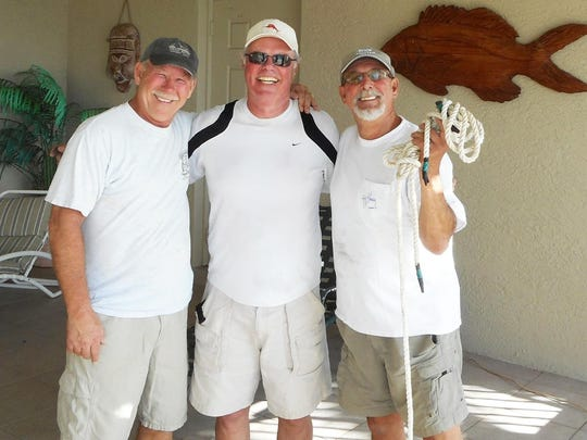 "Marco Towers neighbors Les McCaughey, left, Gary Knapp and John DeMarco also called ""dock master,"" worked together to save the Walsh family's boat after the storm blew it from its lift."