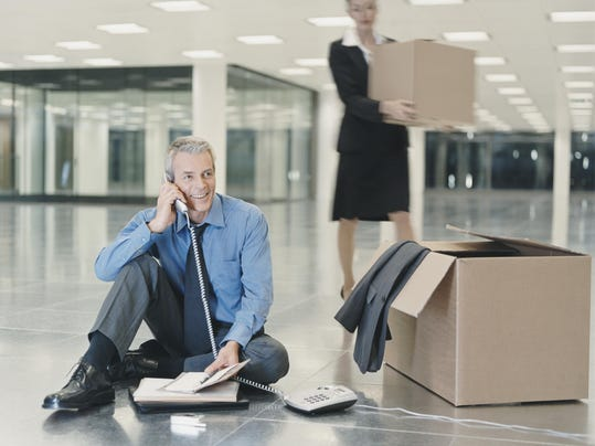 Businessman Sits on the Floor of a New Office, Talking on the Phone, a Woman Carrying a Cardboard Box in the Background