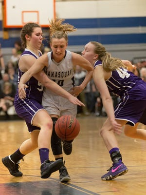 Manaquan's Dara Mabrey drives between Rumson's Megan Volker and Makenna Maquire during first half action. Rumson-Fair Haven vs Manasquan Girls Basketball in the Central Group II championship game in Manasquan, NJ on March 8, 2016