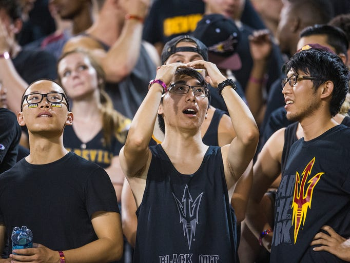 Arizona State student Bryan Chen, 23, holds his hands to his face in disbelief after UCLA's Ishmael Adams intercepted a pass and ran it back for a touchdown with a couple of seconds left in the first half of a game on Thursday, Sept. 25, 2014, at Sun Devil Stadium in Tempe, Ariz.