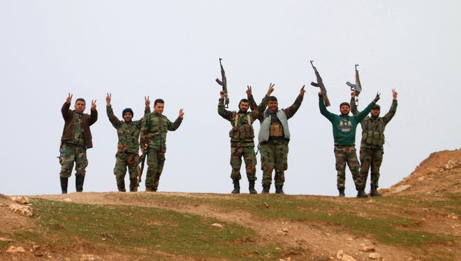 Syrian government forces  raise their weapons  after taking control of the village of Kiffin on the northern outskirts of the embattled city of Aleppo on Feb. 11, 2016.