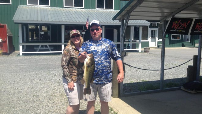 """Newlyweds Jim and Marion Langlois of Brandon celebrate their Lake Champlain honeymoon Saturday by weighing in a standings-leading 5.80 pound largemouth bass in the 34th Annual LCI Father's Day Fishing Derby. The couple got married to coincide with the LCI stating it was the best way they knew to celebrate each other's """"perfect catch."""""""