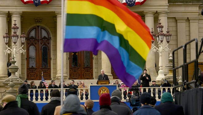 Bob Fluke of Lansing holds a rainbow flag Thursday, January 1, 2015, during Governor Rick Snyder's second inaugural ceremony at the Capitol in Lansing.