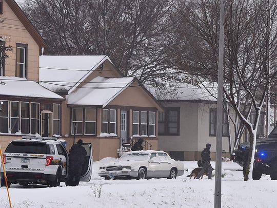 St. Cloud Police and S.W.A.T. team members surround a house on 10th Avenue North Tuesday in St. Cloud during a standoff.