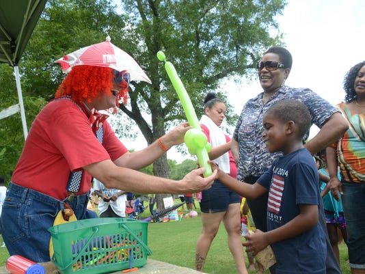 ANI Juneteenth Family Event Curly the Clown (left) presents Aaron Brevelle, 7, with a balloon sword at the Children's Fun in the Park at Frank O. Hunter Park which was part of the Juneteenth celebrations held Saturday, June 20, 2015. Aaron was with his gra